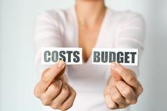 Budżeta planistyczny pojęcie z kobietą wręcza mienia dwa wydruk z kosztem i budżetem obrazy royalty free