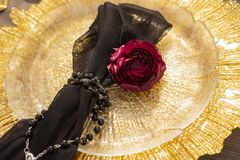 The bud of a red rose, lying on a golden plate, next to a black. Veil, girded with a necklace. Decoration, gothic wedding. Copy space Stock Image