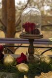 The bud of a red rose, lying on a golden plate and a golden spoo. N and knife, dezhashi on an old wooden table. Decoration, gothic wedding. Copy space Royalty Free Stock Photos