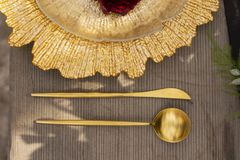 The bud of a red rose, lying on a golden plate and a golden spoo. N and knife, dezhashi on an old wooden table. Decoration, gothic wedding. Copy space Royalty Free Stock Images