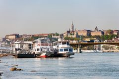 Buda Castle, FSt. Matthias church and Fishermen`s Bastion viewed. From Danube river with ships in the foreground stock photos