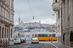 Buda Castle seen from Pest with a tram and a car passing in front. The castle is historical palace complex of the Hungarian kings royalty free stock images