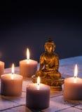 Buda de bronce con las velas encendidas calientes para el concepto de mindfulness Fotos de archivo