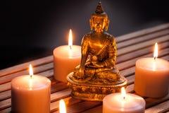 Buda de bronze com velas iluminadas mornas sobre o fundo de madeira Imagem de Stock