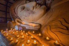Buda de descanso con la vela se enciende en el templo de Shwesandaw Imagen de archivo libre de regalías