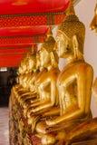 Buda de oro hermoso en el pedestal, algunas paredes blancas fotos de archivo libres de regalías