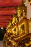 Buda de oro hermoso en el pedestal, algunas paredes blancas imagen de archivo