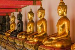 Buda de oro hermoso en el pedestal, algunas paredes blancas imagenes de archivo