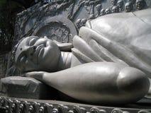 Buda deslizando e de sorriso em cores cinzentas no templo em Vietname Fotos de Stock Royalty Free