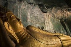 Buda dourada de reclinação na caverna Foto de Stock Royalty Free