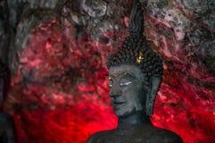 A Buda, em cavernas antigas, luz vermelha brilha através da parte traseira imagem de stock