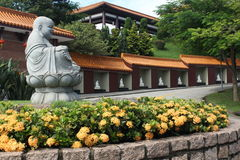 Buda and Flowers. Zu Lai Temple Environment in Sao Paulo. Buda in Foreground Stock Photos