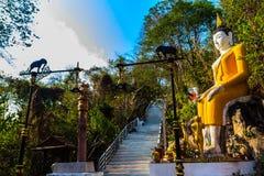 Buda grande amarillo en la manera de la escalera a la colina en Wat Khao Rup Chang o el templo de la colina del elefante, uno del Foto de archivo libre de regalías