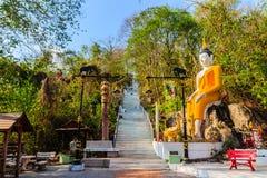 Buda grande amarillo en la manera de la escalera a la colina en Wat Khao Rup Chang o el templo de la colina del elefante, uno del Foto de archivo