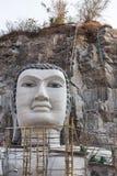 Buda grande talló de piedra en la montaña bajo construcción en templo tailandés público Fotografía de archivo