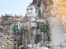 Buda grande talló de piedra en la montaña bajo construcción en templo tailandés público Imagenes de archivo