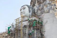 Buda grande talló de piedra en la montaña bajo construcción en templo tailandés público Fotos de archivo