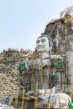Buda grande talló de piedra en la montaña bajo construcción en templo tailandés público Imágenes de archivo libres de regalías