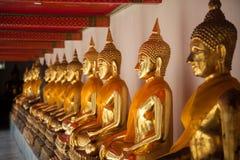 Buda que senta-se na linha e que medita o templo de Wat Pho, Banguecoque, Fotografia de Stock Royalty Free