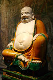 Budai a fat smiling Buddha monk. Glazed stoneware Ming dynasty figure dating from AD 1486 of Budai a fat smiling monk often regarded at the future Buddha which Stock Image