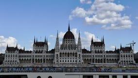 Budapest, abril de 2019: Timelapse de las nubes que se mueven sobre el edificio del parlamento visto de enfrente del río Danubio  metrajes