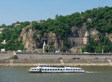 Budapest, boat on the Danube river. Boat on the Danube river with the Gellert hill in the background, Budapest, Hungary Stock Images