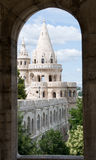 Budapest castle towers through round-headed window. Fairytale looking Budda castle towers through  round-headed window of a tower Stock Photo
