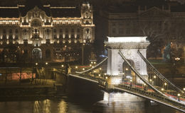 Budapest chain bridge by night winter danube shore. Budapest famous chain bridge by night on danube shore with buildings in background Royalty Free Stock Photo