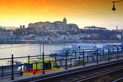 Budapest Danube riversides. Danube river tourist boats station,embankment traffic ,opposite bank  Buda Castle and bright yellow sunset skies, Budapest Hungary Royalty Free Stock Photos