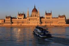 Budapest, el parlamento húngaro con el barco en el Danubio en la puesta del sol Fotos de archivo libres de regalías