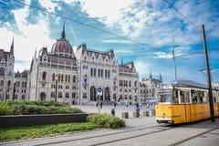 Budapest Hungagry - september, 11, 2018 - gula spårvagnpasserande framme av den ungerska parlamentet royaltyfri fotografi