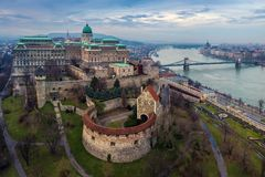 Budapest, Hungary - Aerial drone skyline view of Buda Castle Royal Palace with Szechenyi Chain Bridge. And Parliament of Hungary on a cloudy winter day stock images