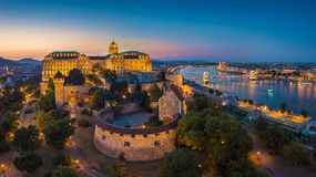 Budapest, Hungary - Aerial panoramic skyline view of beautiful illuminated Buda Castle Royal Palace with Szechenyi Chain Bridge. Hungarian Parliament at blue stock photography