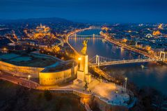 Budapest, Hungary - Aerial panoramic view of Budapest at blue hour. This view includes illuminated Statue of Liberty. On Gellert Hill, Buda Castle Royal Palace royalty free stock image