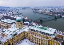 Budapest, Hungary - Aerial panoramic view of the snowy Buda Castle Royal Palace from above with the Szechenyi Chain Bridge royalty free stock image