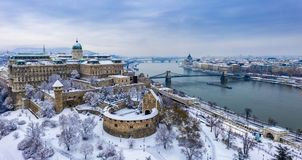 Budapest, Hungary - Aerial panoramic view of the snowy Buda Castle Royal Palace from above with the Szechenyi Chain Bridge royalty free stock photography