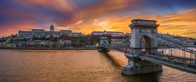 Budapest, Hungary - Aerial panoramic view of Szechenyi Chain Bridge with Buda Tunnel and Buda Castle Royal Palace. At background with a dramatic colorful sunset royalty free stock photo