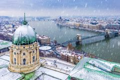 Budapest, Hungary - Aerial view of the dome of snowy Buda Castle Royal Palace from above with the Szechenyi Chain Bridge stock image