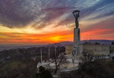 Budapest, Hungary - Aerial view of the Hungarian Statue of Liberty with Buda Hills and amazing colorful sunset. Behind at winter time royalty free stock images