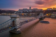 Budapest, Hungary - Aerial view of Szechanyi Chain Bridge and Buda Castle Royal Palace with a beautiful dramatic golden sunset. And sightseeing boat on River royalty free stock images