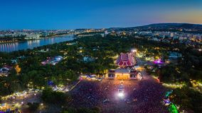 BUDAPEST, HUNGARY - AUGUST 12, 2018: Aerial panoramic photograph of Sziget Festival and main stage. With the skyline of Budapest at background at blue hour royalty free stock image