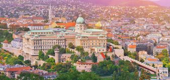 Budapest, Hungary. Beautiful aerial view of historic Buda Castle Royal Palace and South Rondella at sunrise with blue sky and stock photos