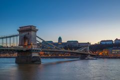 Budapest, Hungary - Beautiful Szechenyi Chain Bridge over River Danube and Buda Castle Royal Palace. At blue hour with clear blue sky stock photo