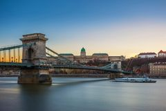 Budapest, Hungary - Beautiful Szechenyi Chain Bridge with sightseeing boat on River Danube. And Buda Castle Royal Palace at blue hour with clear blue sky Stock Photo
