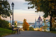 Budapest, Hungary - Bench and autumn foliage on the Buda hill with the Hungarian Parliament. And Chain Bridge at background royalty free stock photo