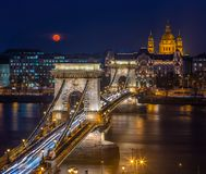 Budapest, Hungary - Blood Moon rising over downtown of Budapest with beautiful Szechenyi Chain Bridge and St. Stephen`s Basilica royalty free stock photo