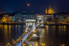 Budapest, Hungary - Blood Moon rising over downtown of Budapest with beautiful Szechenyi Chain Bridge and St. Stephen`s Basilica royalty free stock image