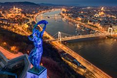 Budapest, Hungary - Blue illuminated Hungarian statue of liberty on World Autism Awareness Day with skyline of Budapest. At background at dusk stock photography