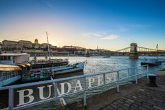 Budapest, Hungary - Boats on River Danube with Buda Castle Royal Palace and Szechenyi Chain Bridge. At sunset with clear blue sky stock photography