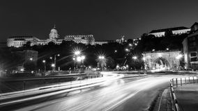 Car traffic trail lights with illuminated Chain bridge and Buda Castle in Budapest, Hungary at night. Black and white. Budapest, Hungary. Car traffic trail stock images